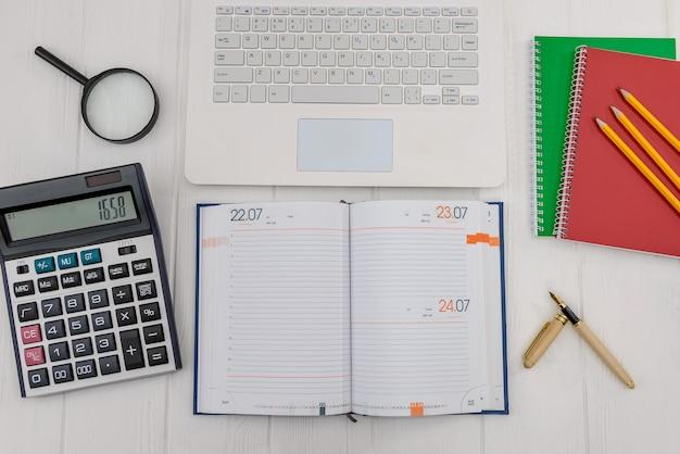 Tagebuch mit laptop auf schreibtisch, arbeitsplatzkonzept