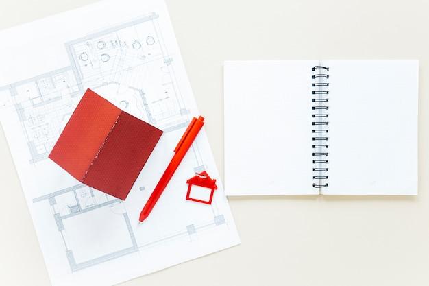 Tagebuch mit plan und hausmodell auf immobilienschreibtisch öffnen