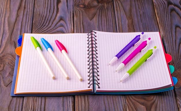 Tagebuch (notizbuch) und farbige stifte auf holztisch.