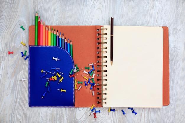 Tagebuch (notizbuch) und farbstifte auf holztisch.