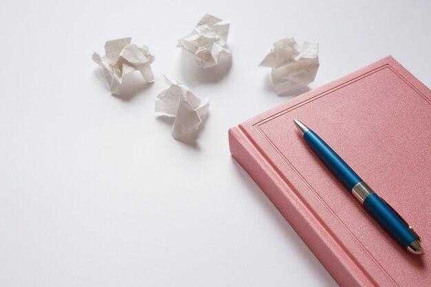 Tagebuch und metallstift auf weißem tisch zerknittertes papier. fehler im brief