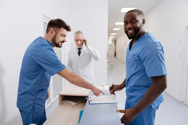 Tagesbericht unterschreiben. lächelnde qualifizierte optimistische praktizierende, die in der klinik arbeiten und eine erklärung unterschreiben, während ein älterer kollege im hintergrund telefoniert