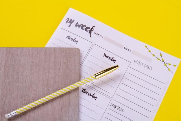 Tagesplanungspapier mit buch und bleistift.