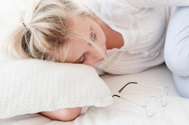 Tagesschlafentspannung. junge blonde frau schlafen zusammenrollen. gläser in der nähe.