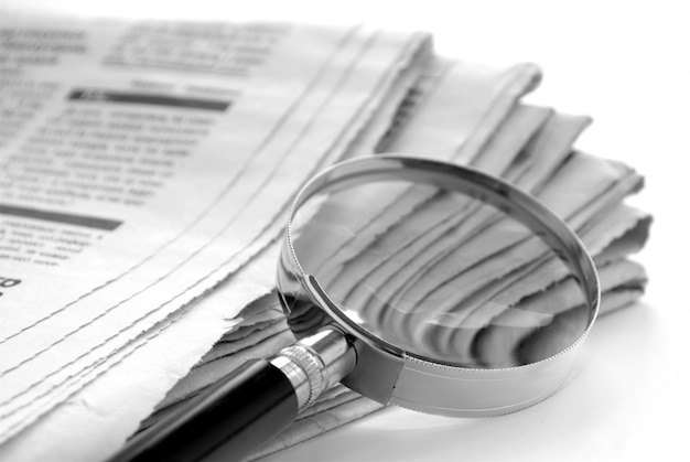 Tageszeitung und eine lupe, um nachrichten zu finden
