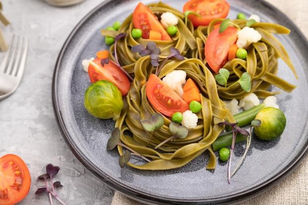 Tagliatelle grüne spinatnudeln mit tomaten, erbsen und mikrogrünen sprossen