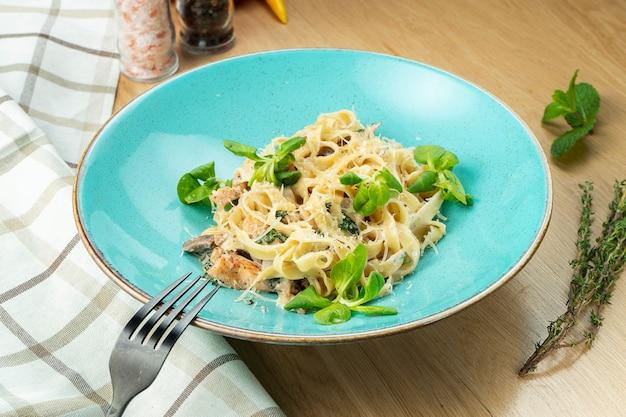 Tagliatelle mit huhn, weißer soße und parmesan in der blauen schüssel auf hölzernem hintergrund.