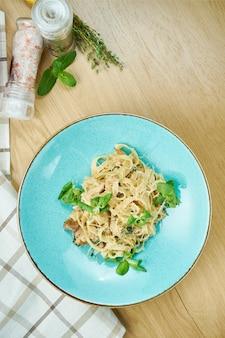 Tagliatelle mit huhn, weißer soße und parmesan in der blauen schüssel auf holztisch. traditionelle hausgemachte italienische pasta. nahansicht
