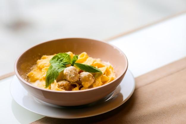 Tagliatelle mit kaninchenfleischbällchen frikadellen in einer cremigen sauce mit nudeln pasta mit fleisch und parmesankäse spaghetti mit fleischbällchen und parmesan italienische pasta zum mittagessen pasta in einer schüssel abendessen