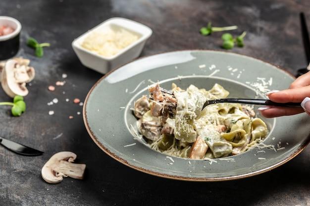 Tagliatelle-nudeln mit champignons und hühnchen in cremiger käsesauce. restaurantmenü, diät, kochbuchrezept.