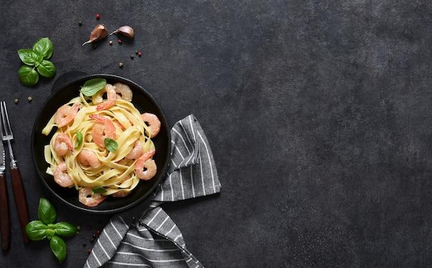 Tagliatelle-nudeln mit cremiger soße und garnelen in einer pfanne auf dem küchentisch auf einem schwarzen hintergrund. von oben betrachten.