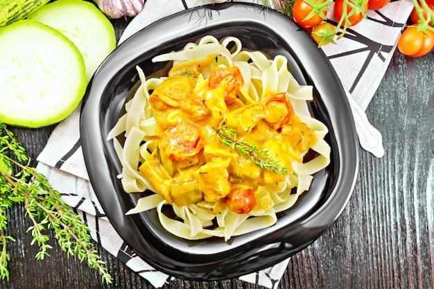 Tagliatelle nudeln mit fleischgulasch, tomate, zucchini und thymian in einem teller auf serviette