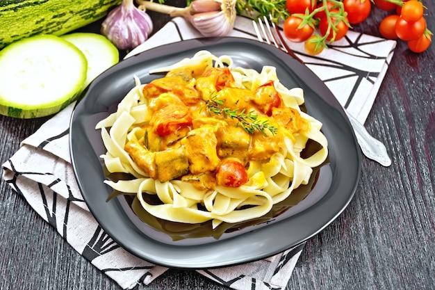 Tagliatelle nudeln mit fleischgulasch, tomate, zucchini und thymian