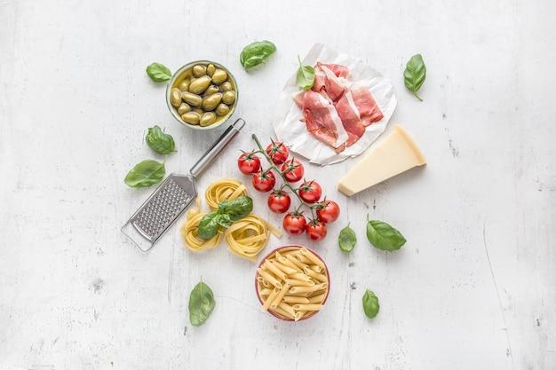 Tagliatelle pene pasta oliven olivenöl tomaten parmesankäse prosciutto und basilikumblätter