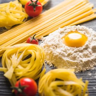 Tagliatelle und spaghetti nudeln mit eigelb auf mehl