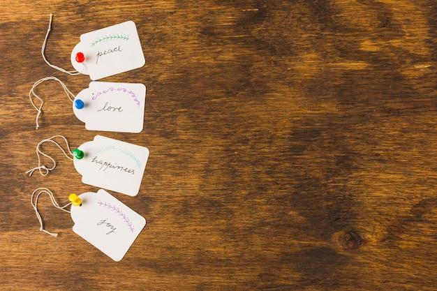 Tags mit handschriftlichen nachrichten, die durch push-pins auf einem hölzernen schreibtisch in reihe stecken