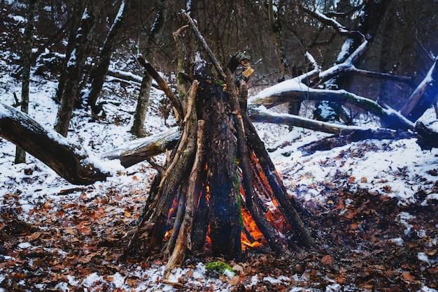 Tagsüber großes lagerfeuer im winterwald