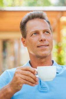 Tagträumen mit tasse kaffee. fröhlicher reifer mann, der kaffee trinkt und lächelt, während er draußen mit haus im hintergrund sitzt