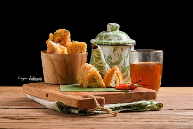 Tahu susur werden auf einem schneidebrett mit stücken serviert, die den inhalt zeigen. ist ein traditionelles essen aus indonesien, hergestellt aus gebratenem tofu, gefüllt mit gebratenem gemüse, umwickelt in mehlteig