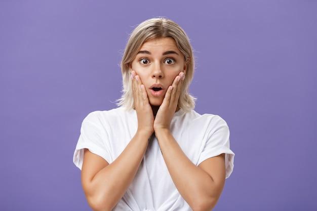 Taille-aufnahme von fassungslos beeindruckten wunderschönen gebräunten frau in weißem t-shirt mit blonden haaren mit offenem mund nach luft schnappen vor überraschung händchenhalten auf wangen vor erstaunen und neugier