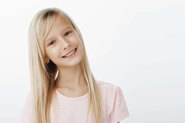Taille-aufnahme von sorglosem freudigem kaukasischem mädchen mit blondem haar, kippendem kopf und breitem lächeln, zufrieden und glücklich zu sein, während sie mit einem mann aus der schule spricht, den sie mag, der über grauer wand steht
