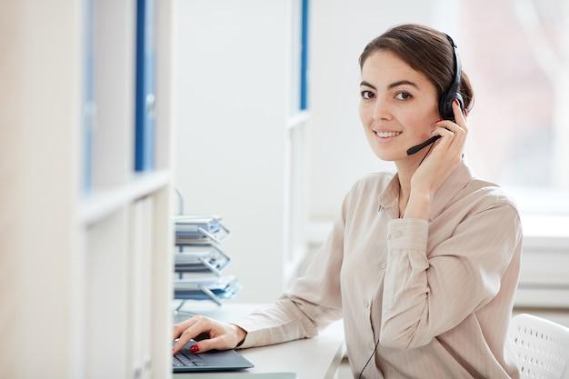 Taille bis porträt der lächelnden geschäftsfrau, die mit mikrofon spricht und schaut, während mit laptop im büroinnenraum arbeitet