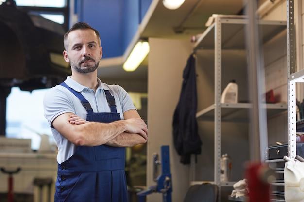 Taille bis porträt des muskulösen automechanikers, der mit verschränkten armen steht, während er im garagenladen aufwirft, kopieren raum