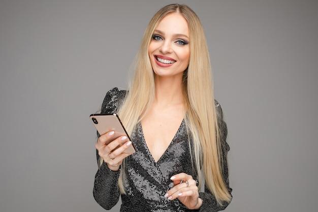 Taille der glücklichen blonden dame im schwarzen kleid, das mit smartphone aufwirft