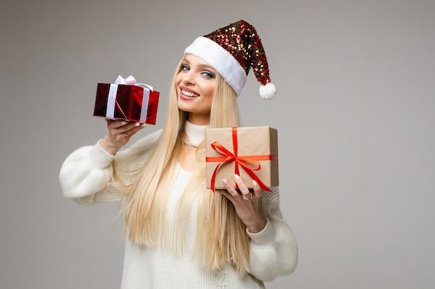 Taille der glücklichen blonden dame in der weihnachtsmütze, die weihnachten feiert