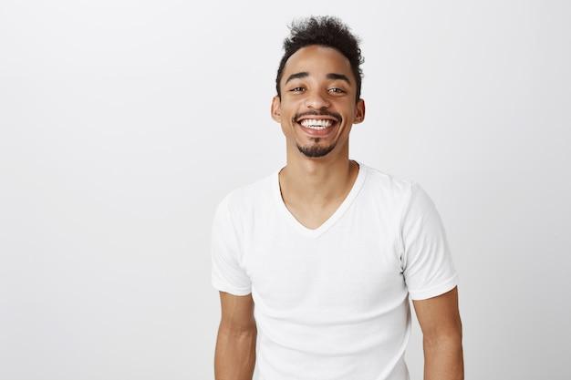 Taille des hübschen lächelnden afroamerikanermannes im weißen lässigen t-shirt, das glücklich schaut