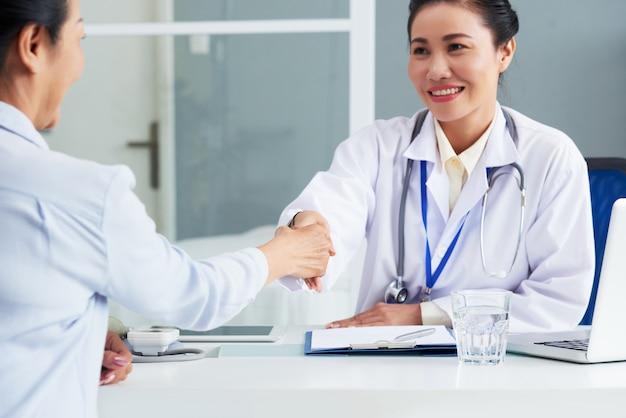 Taille herauf das porträt asiatischen doktors hände mit dem unerkennbaren patienten rüttelnd, der seins zurück zu der kamera sitzt