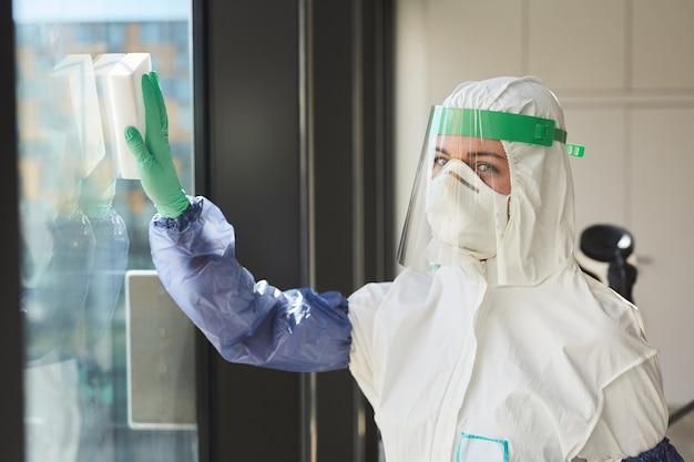 Taille hoch porträt der arbeiterin, die hazmat-anzug trägt, während fenster wäscht und büro desinfiziert,