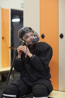 Taille hoch porträt der hockeyspielerin, die helm in umkleideraum aufsetzt