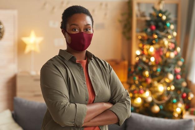 Taille hoch porträt der jungen afroamerikanischen frau, die maske trägt und kamera betrachtet, während weihnachten feiert, raum kopieren