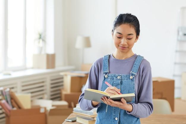 Taille hoch porträt der jungen asiatischen frau, die im planer schreibt, während sie im neuen haus oder in der neuen wohnung mit pappkartons steht