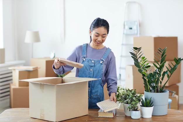 Taille hoch porträt der jungen asiatischen frau, die pappkarton packt oder auspackt und glücklich lächelt, während sie in neues zuhause zieht