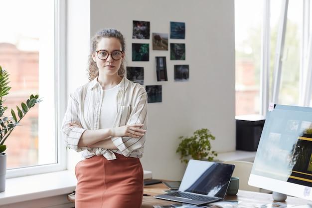 Taille hoch porträt der kreativen jungen frau, die kamera beim stehen mit den armen durch schreibtisch im modernen büroinnenraum, kopierraum steht