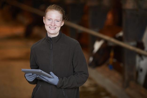 Taille hoch porträt der lächelnden jungen frau, die in der scheune steht, während an der milchfarm arbeitet und tablette hält, kopiert raum