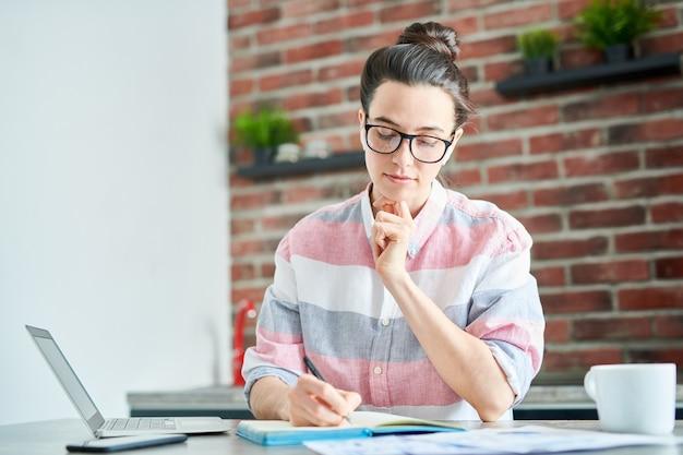 Taille hoch porträt der modernen jungen frau, die zu hause studiert und in notizbuch schreibt