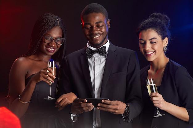 Taille hoch porträt der multiethnischen gruppe von freunden, die smartphone-bildschirm während der eleganten party betrachten