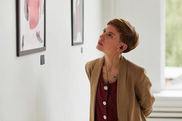 Taille hoch porträt der tätowierten jungen frau, die gemälde betrachtet und audioguide bei der ausstellung der modernen kunstgalerie hört,