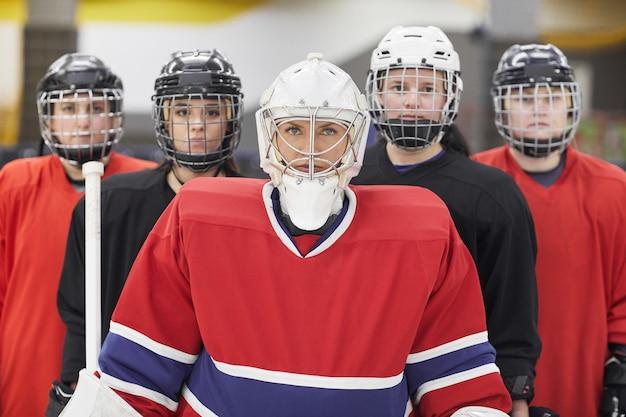 Taille hoch porträt der weiblichen eishockeymannschaft, die kamera betrachtet