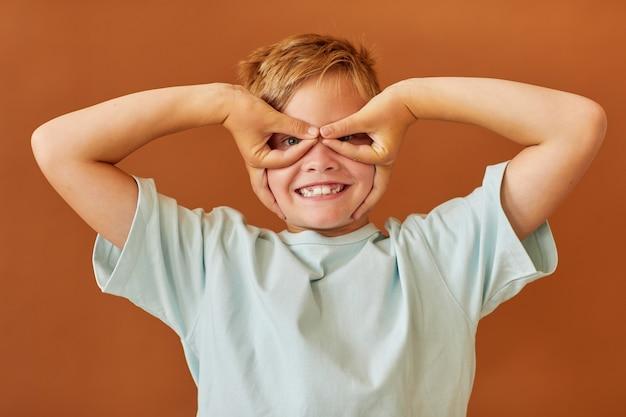 Taille hoch porträt des blonden teenagers, der gesichter an der kamera macht und wie ein superheld aufwirft, während er gegen einfache braune oberfläche im studio steht