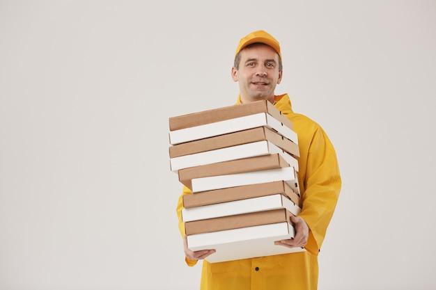 Taille hoch porträt des erwachsenen lieferboten, der pizzaschachteln hält und fröhlich lächelt