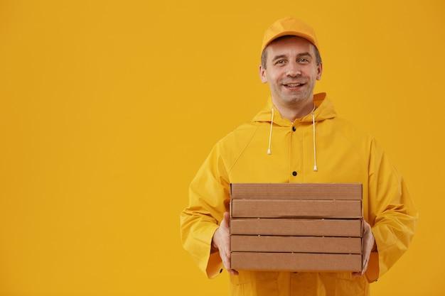Taille hoch porträt des erwachsenen lieferers, der pizzaschachteln hält