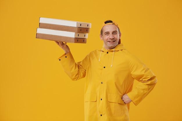Taille hoch porträt des fröhlichen liefermanns, der pizzaschachteln hält