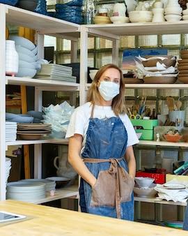 Taille hoch porträt des fröhlichen weiblichen handwerkers mit gesichtsmaske, die im keramikstudio aufwirft