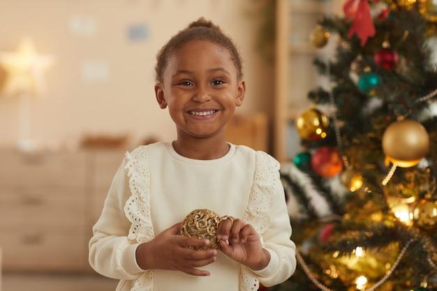 Taille hoch porträt des glücklichen afroamerikanischen mädchens, das zu hause am weihnachtsbaum steht und in die kamera lächelt