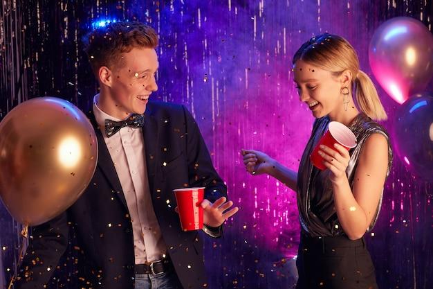 Taille hoch porträt des glücklichen teenagerpaares, das in der dekorierten halle tanzt und rote tassen hält, während abschlussballnacht oder party genießen