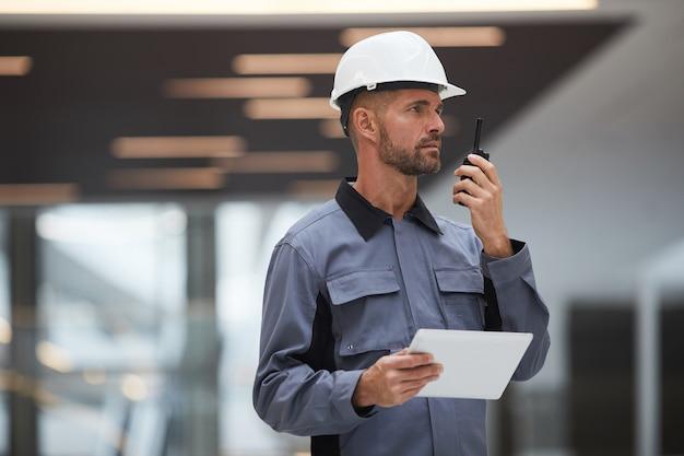 Taille hoch porträt des hübschen reifen arbeiters, der durch walkie-talkie spricht, während arbeit auf der baustelle oder in der industriewerkstatt überwacht wird